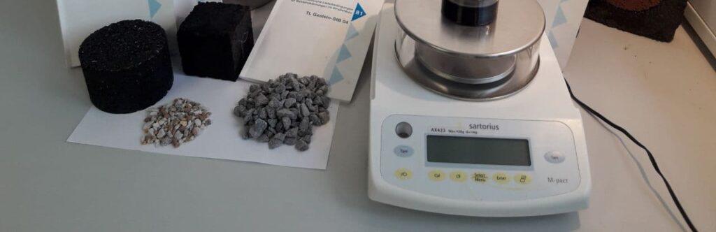 Unser Labor sichert die Qualität der Baustoffe Gestein und Asphalt. Im Bild sind Regelwerke und Proben zu sehen.